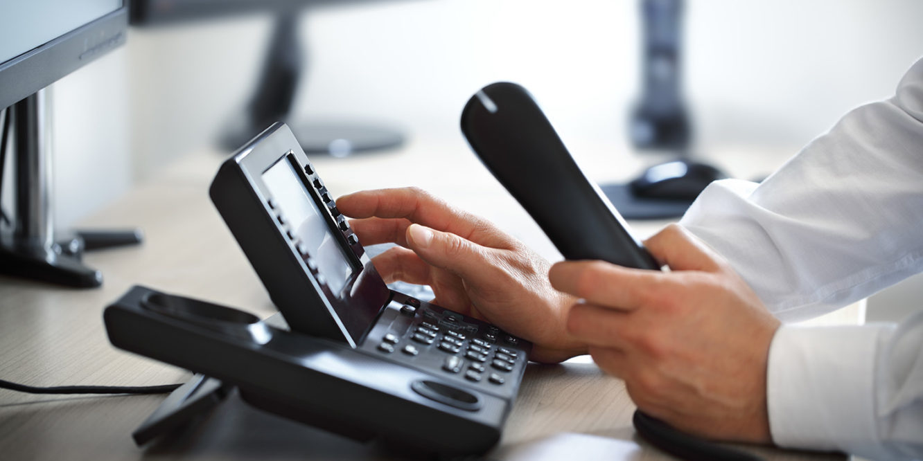 Business person dialing telephone keypad